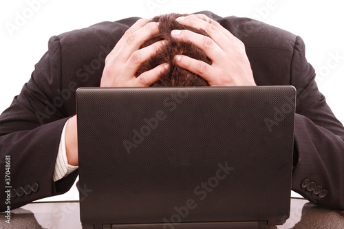 a successful business man is frustrated on a table with a laptop