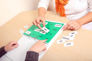 Hände und Wortrainer beim Logopäden