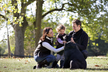 Parents and little girl cuddling dog