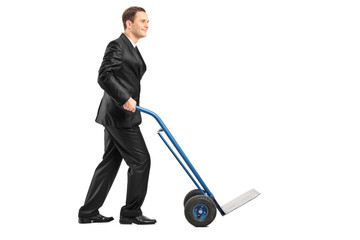 Smiling businessman pushing an empty handtruck