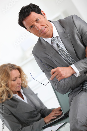 Businessman sitting on the desk of a colleague