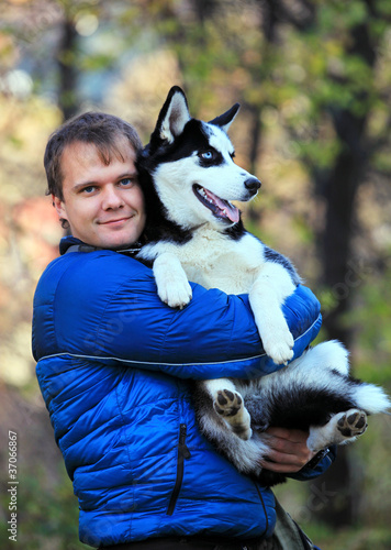 Portrait of young man holding his husky dog outdoors