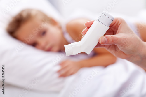 Sick kid with inhaler in foreground