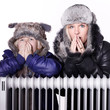 Mother and daughter in warm winter coats leaning over a radiator