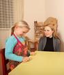 Lächelndes Kleinkind sitzt mit lächelnder Mutter am Tisch