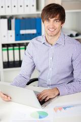 mann arbeitet am laptop im büro