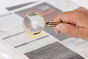 man using magnify glass looking for jobs