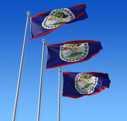 Three flags of Belize against blue sky.