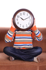 Young child with big clock covering face