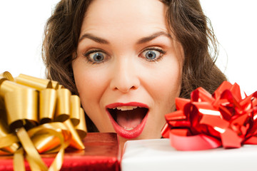 Beautiful surprised woman looking at christmas gifts