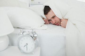 Man covering his ears while his alarm clock is ringing