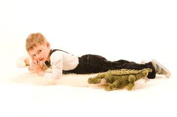 Мальчик лежит на полу с игрушечным крокодилом