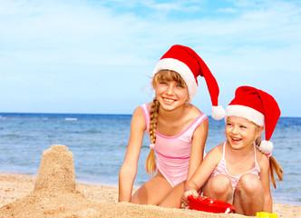 Children in santa hat playing on  beach.