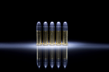 Several .22 caliber bullets on black background