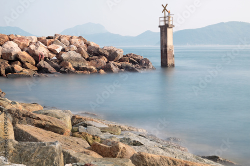 Lighthouse on a Rocky Breakwall: A small lighthouse warns of a r