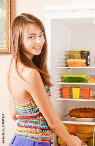 young woman taking fruit out of fridge