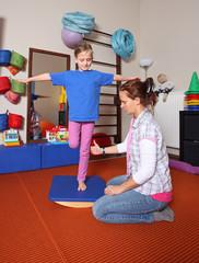 Gleichgewichtsübung beim Physiotherapeuten auf dem Schaukelbrett