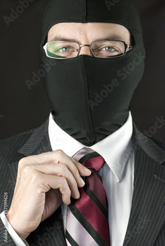 Businessman In Balaclava Straightens Tie