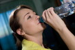 girl drinks water from a bottle after fitness