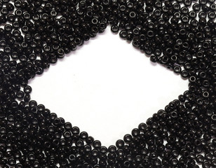 black pearls scattered on a white background with place for text