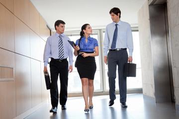 Businesspeople Walking In Office Corridor