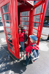 Boy talking in pay phone box