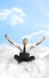 Happy young businessman with laptop sitting on the clouds