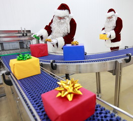 Two Santa Clauses working in Xmas Presents Factory