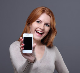 young woman showing mobile phone against grey background