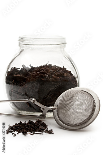 Glass container with tea and a tea strainer