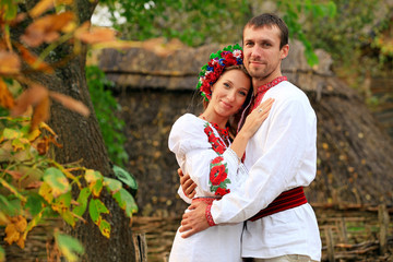 Lovely couple in Ukrainian national costumes outdoors