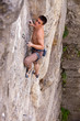 Rock climber fastening rope to quick-draw and looking up