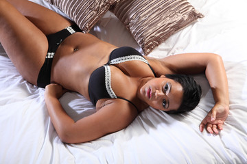 Curvy african american woman in bed lingerie
