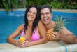 Pareja hispana en una piscina comiendo frutas.