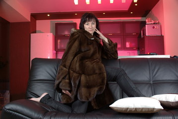 Attractive woman in a fur coat on the sofa