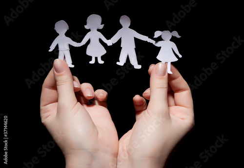 Paper chain family in hands on black background