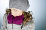 A young woman wearing hat and gloves, trying to keep warm