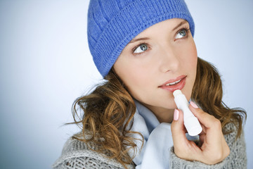 A young woman applying lip balm, in wintertime