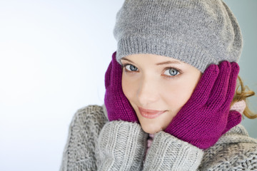 A young woman with her hands over her ears, trying to keep warm