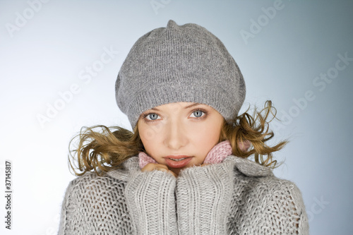A young woman wearing a grey woollen hat, keeping warm