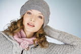 Portrait of a young woman wearing a grey woollen hat
