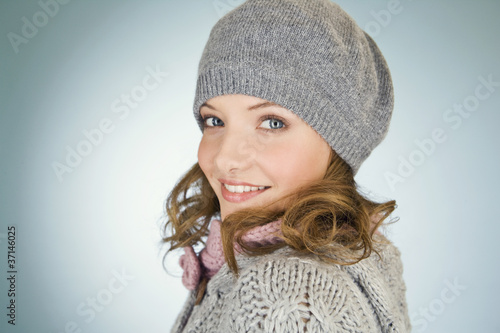 A woman wearing a grey woollen hat, looking over her shoulder