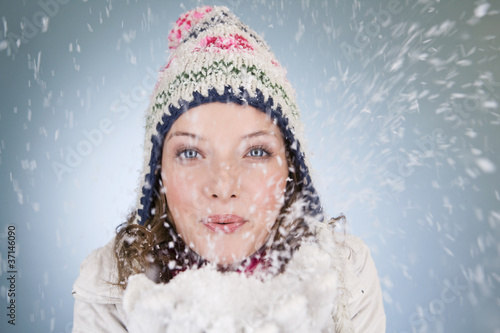 A young woman blowing a handful of snowflakes