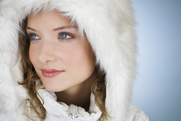 A woman wearing a winter coat with a fur hood, close-up