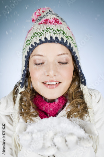 A young woman holding a handful of snow