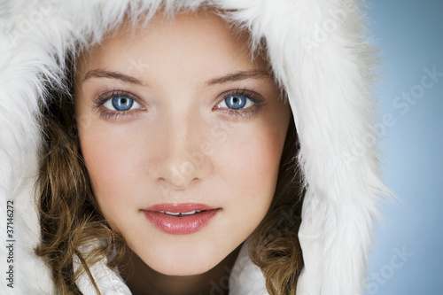 A young woman wearing a winter coat with a fur hood, close-up
