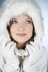 A young woman wearing a winter coat with a fur hood , looking up