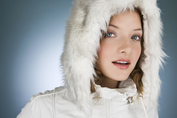 A young woman wearing a winter coat with a fur hood