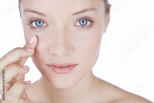 A young woman with blue eyes, finger touching her face