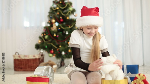 Preschooler girl in santa cap gets a teddy bear for Christmas